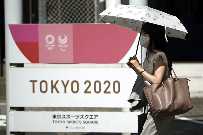A woman wearing a face mask to help curb the spread of the coronavirus walks in front of Tokyo 2020 sign Friday, Sept. 4, 2020, in Tokyo. The CEO of the Tokyo Olympics Toshiro Mut said Friday that having a vaccine is not a requirement for holding next year Olympics and Paralympics. (AP Photo/Eugene Hoshiko)