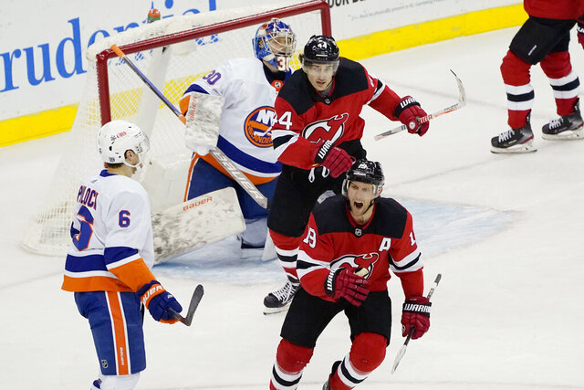 New Jersey Devils center Travis Zajac (19) and Devils left wing Miles Wood (44) react after Devils center Jack Hughes scored a goal against New York Islanders goaltender Ilya Sorokin (30) during the first period of an NHL hockey game against the New York Islanders, Sunday, Jan. 24, 2021, in Newark, N.J. Islanders defenseman Ryan Pulock (6) takes in the reaction. (AP Photo/Kathy Willens)