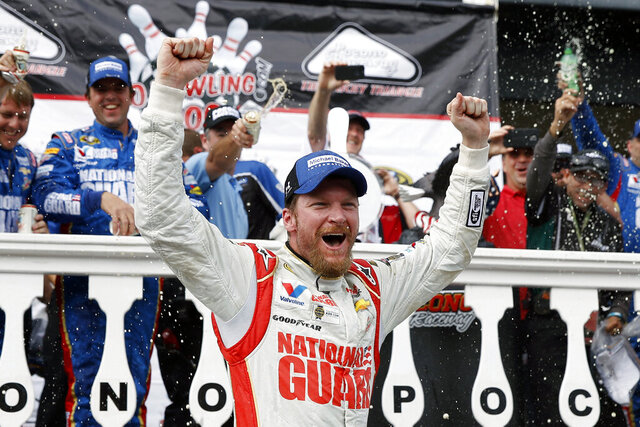 FILE - In this Aug. 3, 2014, file photo, Dale Earnhardt Jr. celebrates in Victory Lane after winning a NASCAR Sprint Cup Series auto race at Pocono Raceway in Long Pond, Pa. Longtime fan favorite Dale Earnhardt Jr. is expected to be the marquee name on NASCAR's 2021 Hall of Fame class, to be announced Tuesday, June 16, 2020. (AP Photo/Matt Slocum, File)