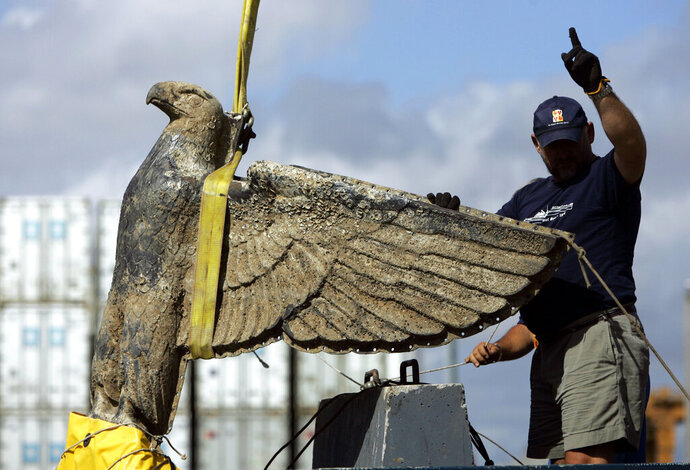 FILE- In this Feb. 10, 2006 file photo, an Uruguayan worker directs the salvage the eagle of World War II German pocket battleship Admiral Graf Spee, in Montevideo, Uruguay. A court in Uruguay has ruled on Friday, June 21, 2019, that the government must sell the huge bronze Nazi eagle with a swastika under its talons that was part of the stern of the Graf Spee. (AP Photo/Marcelo Hernandez, File)