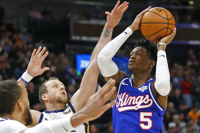 Sacramento Kings guard De'Aaron Fox (5) shoots as Utah Jazz forward Joe Ingles defends during the first half of an NBA basketball game Saturday, Jan. 18, 2020, in Salt Lake City. (AP Photo/Rick Bowmer)