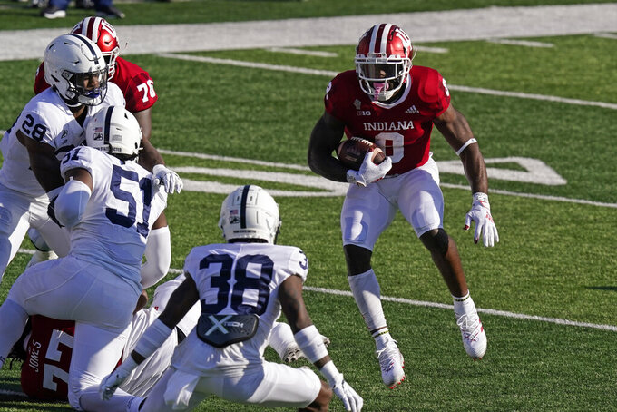 Indiana's Stevie Scott III (8) runs against Penn State's Lamont Wade (38) during the first half of an NCCAA college football game, Saturday, Oct. 24, 2020, in Bloomington, Ind. (AP Photo/Darron Cummings)