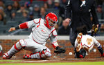 Atlanta Braves' Ozzie Albies (1) scores on a Nick Markakis sacrifice fly as ball gets away from Philadelphia Phillies catcher Jorge Alfaro (38) in the fourth inning of a baseball game Monday, April 16, 2018, in Atlanta. (AP Photo/John Bazemore)