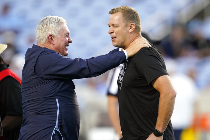 North Carolina coach Mack Brown, left, and Virginia coach Bronco Mendenhall speak prior to an NCAA college football game in Chapel Hill, N.C., Saturday, Sept. 18, 2021. (AP Photo/Gerry Broome)