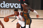 Washington Wizards forward Troy Brown Jr., left, drives against Oklahoma City Thunder guard Luguentz Dort, right, during the first half of an NBA basketball game Sunday, Aug. 9, 2020, in Lake Buena Vista, Fla. (Kim Klement/Pool Photo via AP)