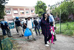 Police evict people from an abandoned school which they had occupied on the outskirts of Rome, Monday, July 15, 2019. Police are evicting migrants and Italians from an abandoned former school on Rome's outskirts in the latest operation to empty occupied buildings of migrants and squatters. (Massimo Percossi/ANSA via AP)