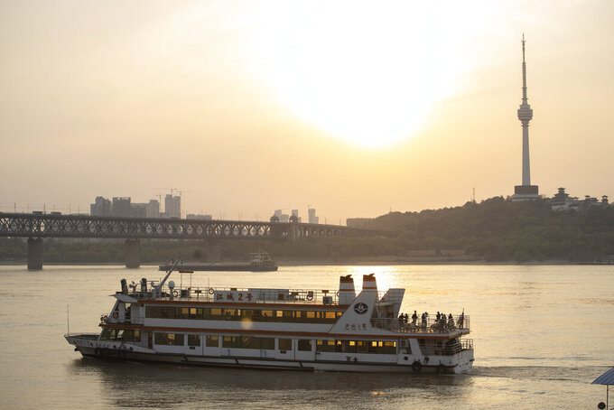 In this April 8, 2020, photo, a ferry crosses the Yangtze River in Wuhan in central China's Hubei province. The reopening of ferry service on the Yangtze River, the heart of life in Wuhan for more than 20 centuries, was an important symbolic step in official efforts to get business and daily life in this central Chinese city of 11 million people back to normal after a 76-day quarantine ended in the city at the center of the coronavirus pandemic. (AP Photo/Ng Han Guan)