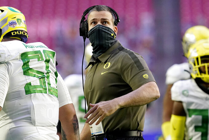 Oregon head coach Mario Cristobal looks at the clock during the first half of the Fiesta Bowl NCAA college football game against Iowa State, Saturday, Jan. 2, 2021, in Glendale, Ariz. (AP Photo/Ross D. Franklin)