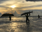 A surfer carries his board ashore as the sun sets over Kata Beach on the resort island of Phuket, Thailand on Sunday, May 26, 2019. Thailand hopes to first fully reopen the island of Phuket, its most popular destination, by July 1 for vaccinated visitors without quarantine. But they will be required to spend a certain time, possibly up to a week, on Phuket before they are allowed to travel elsewhere in Thailand. (AP Photo/Adam Schreck)