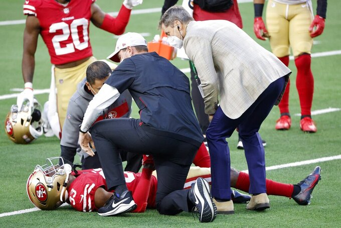 San Francisco 49ers safety Tarvarius Moore (33) receives medical attention from staff members after suffering an unknown injury on a tackle attempt against the Dallas Cowboys in the first half of an NFL football game in Arlington, Texas, Sunday, Dec. 20, 2020. (AP Photo/Michael Ainsworth)