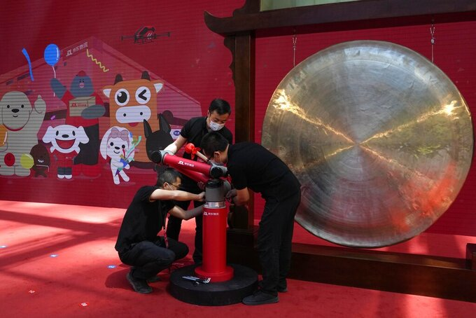 Workers dismantle a robot arm used in sounding a gong at a ceremony to virtually observe the listing of JD Logistics on the Hong Kong stock exchange from the JD.com headquarters in Beijing on Friday, May 28, 2021. JD Logistics' shares jumped 14% in their trading debut Friday in Hong Kong. The company is a subsidiary of Chinese e-commerce giant JD.com. It is the latest technology company to list in the semi-autonomous Chinese city as Beijing intensifies scrutiny of the technology sector. (AP Photo/Ng Han Guan)