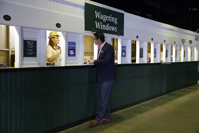 FILE - In this May 2, 2015, file photo, a man places a bet before the 141st running of the Kentucky Derby horse race at Churchill Downs, in Louisville, Ky. Picking a horse to win the Kentucky Derby is easy. Hoping that choice wins and pays off with a profit is the challenge.(AP Photo/Jeff Roberson, File)