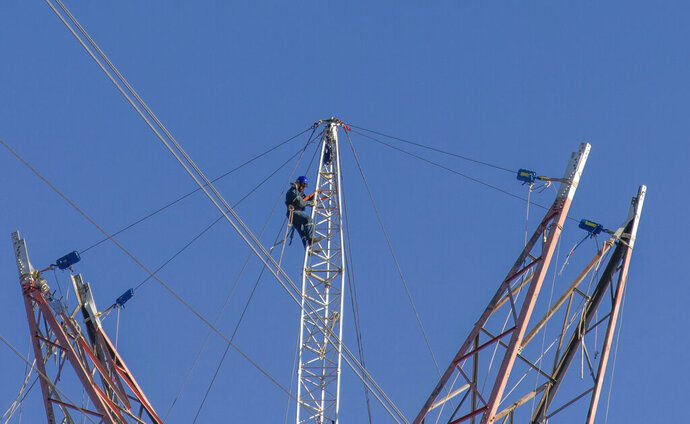 A technician works to continue dismantling Tower 412 and replace it with a new tower, in the Litoral corredor near the town of Zarate, on the border of Buenos Aires and Entre Rios provinces, Argentina, Wednesday, June 19, 2019. Located in the Parana River, Tower 412 hasn't been operational since April while workers were building a new tower to replace it and a bypass system had been set up to handle the current. Argentina's government suggested the origin of Sunday's blackout may stem from this corredor, and hopes to give a detailed explanation of events in twelve days time once all the technical elements have been analyzed. (AP Photo/Tomas F. Cuesta)