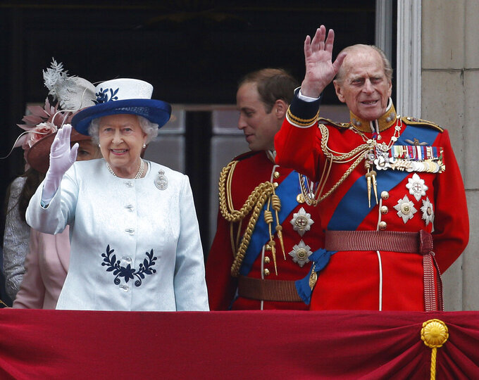 FILE - In this Saturday, June 14, 2014 file photo, Britain's Queen Elizabeth II, accompanied by Prince Philip, wave to the crowds from the balcony of Buckingham Palace, during the Trooping The Colour parade, in central London. Prince Philip was the longest serving royal consort in British history. In Britain, the husband or wife of the monarch is known as consort, a position that carries immense prestige but has no constitutional role. (AP Photo/Lefteris Pitarakis, File)