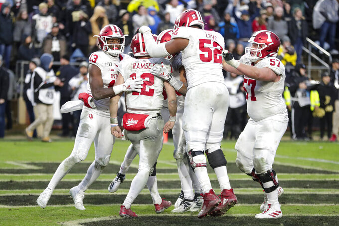 Indiana quarterback Peyton Ramsey (12) is surrounded by teammates after scoring the winning touchdown in the second overtime period of an NCAA college football game against Purdue in West Lafayette, Ind., Saturday, Nov. 30, 2019. Indiana defeated Purdue 44-41 in double overtime. (AP Photo/Michael Conroy)