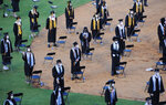 Seniors from Spain Park High School stand on a baseball field at a socially distanced graduation ceremony in Hoover, Ala., Wednesday, May 20, 2020. Health officials say usual graduation ceremonies could endanger the public health by promoting the spread of disease. But school officials say they're using social distancing guidelines and abiding by state health rules. (AP Photo/Jay Reeves)