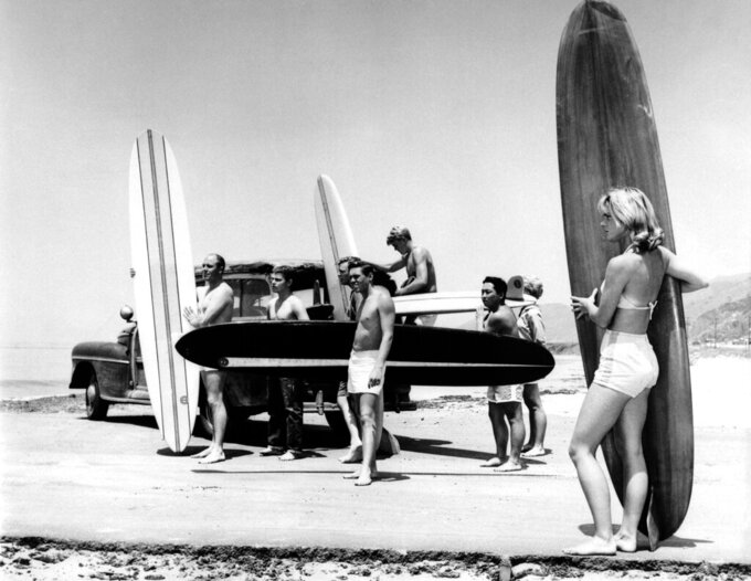 FILE - In this July 12, 1961, file photo, members of the North Bay surfing club upload their surf boards from a station wagon at Malibu Beach, Calif. For some Native Hawaiians, surfing's Olympic debut is both a celebration of a cultural touchstone invented by their ancestors, and an extension of the racial indignities seared into the history of the game and their homeland. The Summer Games in Tokyo, which kick off this month, serve as a proxy for that unresolved tension and resentment, according to the Native Hawaiians who lament that surfing and their identity have been culturally appropriated by white outsiders who now stand to benefit the most from the $10 billion industry. (AP Photo/File)