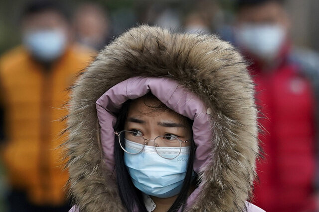 A woman wearing a face mask to help curb the spread of the coronavirus walks on a street during the morning rush hour in Beijing, Tuesday, Dec. 15, 2020. (AP Photo/Andy Wong)
