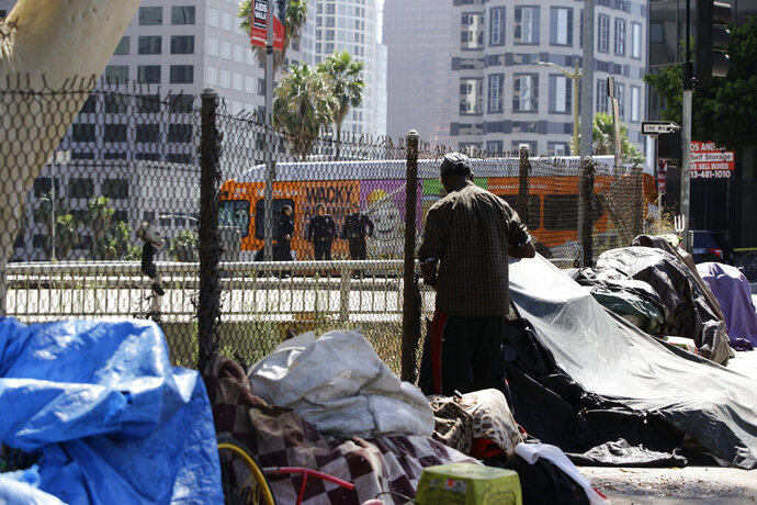 A newly displaced homeless camp is seen while Los Angeles Police officers guard a Harbor Freeway ramp during the visit of President Donald Trump in Los Angeles, Tuesday, Sept. 17, 2019. Trump began a California visit on Tuesday, saying he will do