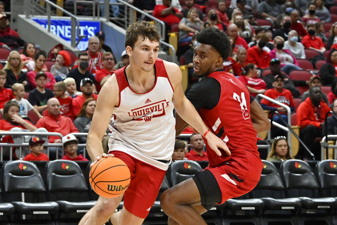 Louisville forward Matt Cross, left, drives past the defense of forward Jae'Lyn Withers (24) during an NCAA college basketball intrasquad game in Louisville, Ky., Saturday, Oct. 16, 2021. (AP Photo/Timothy D. Easley)