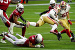 San Francisco 49ers running back Jerick McKinnon is tripped up by Arizona Cardinals linebacker Isaiah Simmons (48) during the second half of an NFL football game, Saturday, Dec. 26, 2020, in Glendale, Ariz. (AP Photo/Rick Scuteri)