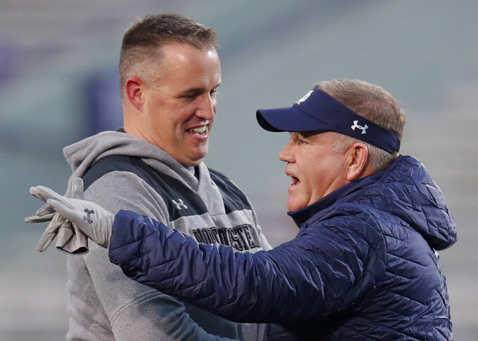 Northwestern's coach Pat Fitzgerald, left, speaks with Notre Dame's coach Brian Kelly before the start of an NCAA college football game Saturday, Nov. 3, 2018, in Evanston, Ill. (AP Photo/Jim Young)