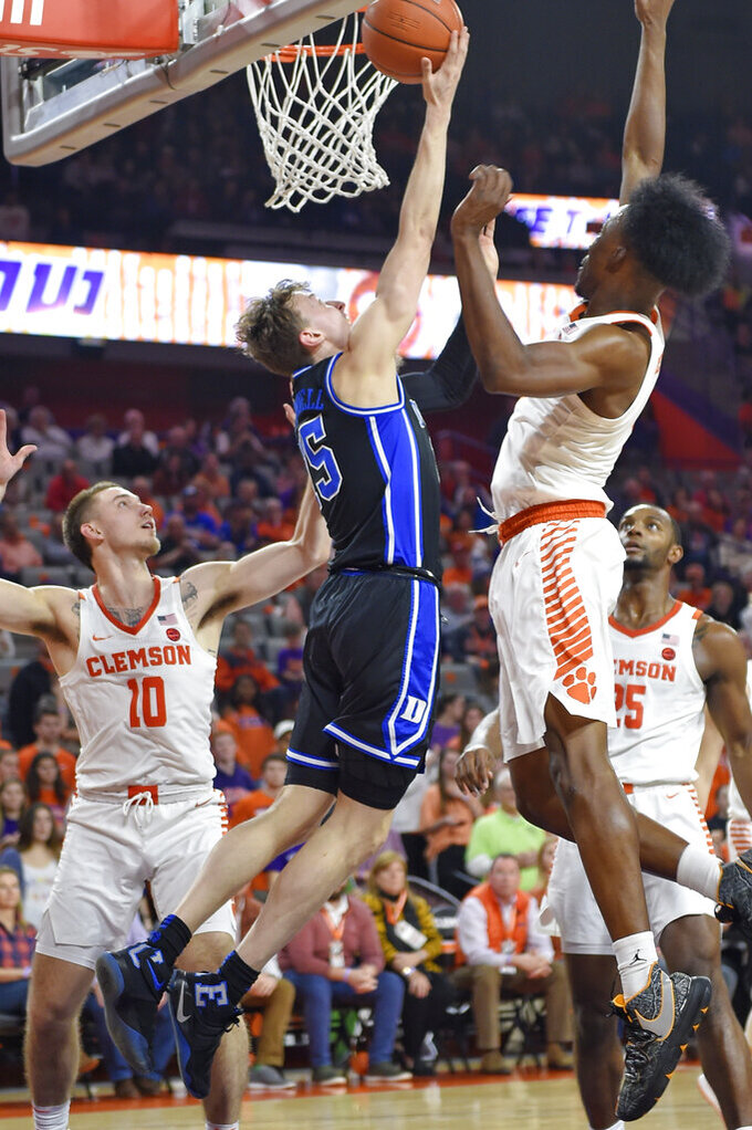 Duke's Alex O'Connell, center, drives to the basket works while defended by Clemson's Curran Scott, left, and John Newman lll during the first half of an NCAA college basketball game Tuesday, Jan. 14, 2020, in Clemson, S.C. (AP Photo/Richard Shiro)
