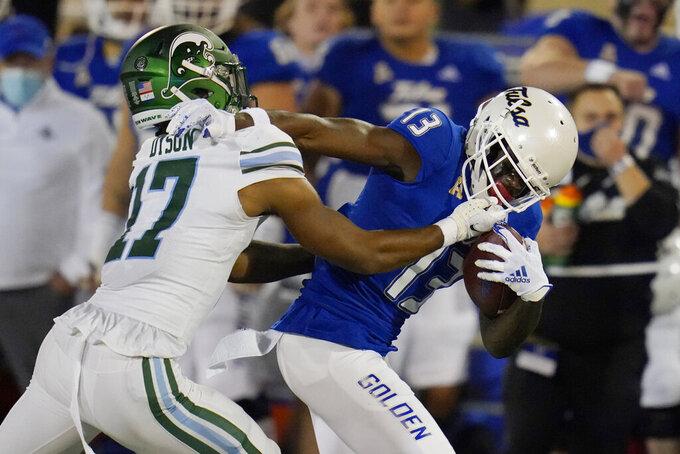 Tulane defensive back Cornelius Dyson (17) grabs the face mask of Tulsa wide receiver Josh Johnson (13) as he tackles Johnson during the second half of an NCAA college football game in Tulsa, Okla., Thursday, Nov. 19, 2020. (AP Photo/Sue Ogrocki)