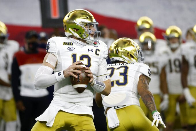 Notre Dame quarterback Ian Book (12) drops back to pass in the first half of the Rose Bowl NCAA college football game against Alabama in Arlington, Texas, Friday, Jan. 1, 2021. (AP Photo/Michael Ainsworth)