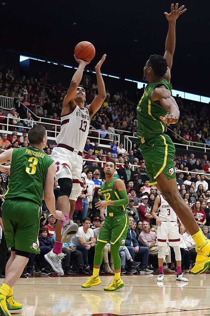 Stanford forward Oscar da Silva (13) pulls up for a shot over Oregon forward Francis Okoro (33) as guard Payton Pritchard (3) watches during the second half of an NCAA college basketball game Saturday, Feb. 1, 2020, in Stanford, Calif. (AP Photo/Tony Avelar)