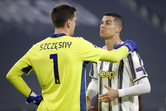 Juventus' Cristiano Ronaldo talks with Juventus' goalkeeper Wojciech Szczesny, left, during the Champions League, round of 16, second leg, soccer match between Juventus and Porto in Turin, Italy, Tuesday, March 9, 2021. (AP Photo/Luca Bruno)