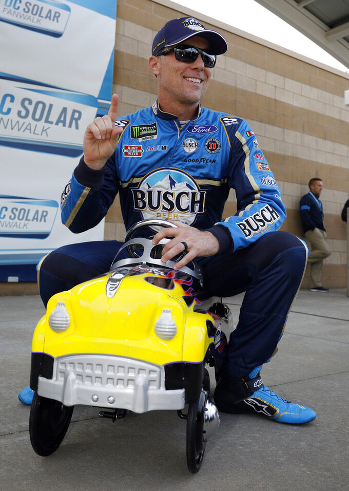 Kevin Harvick celebrates with the speedway pole award following qualifying for a NASCAR Cup Series auto race at Kansas Speedway in Kansas City, Kan., Friday, May 10, 2019. (AP Photo/Colin E. Braley)