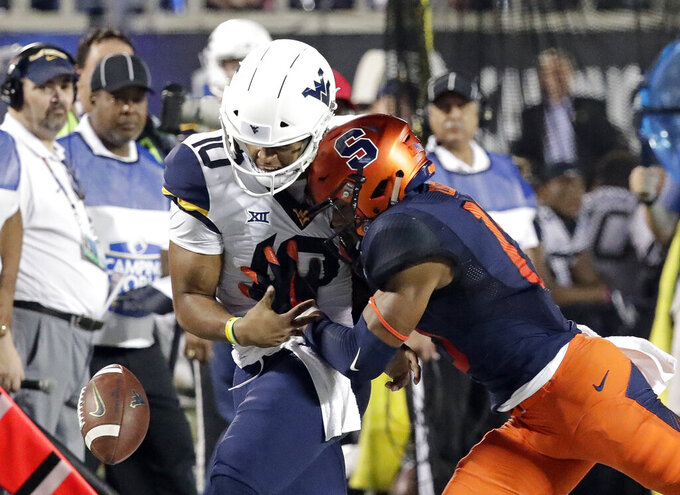 FILE - In this Dec. 28, 2018, file photo, Syracuse defensive back Andre Cisco, right, breaks up a pass intended for West Virginia quarterback Trey Lowe III (10) during the first half of the Camping World Bowl NCAA college football game in Orlando, Fla. Here's a switch for Syracuse coach Dino Babers _ defense rules. Known for his uptempo offenses, the fourth-year coach is looking to his defense to help lift the No. 22 Orange to even greater heights this fall. (AP Photo/John Raoux, File)