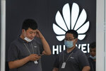 Huawei store workers wait for customers in Beijing on Wednesday, June 2, 2021. Huawei is launching its own HarmonyOS mobile operating system on its handsets as it adapts to losing access to Google mobile services two years ago after the U.S. put the Chinese telecommunications company on a trade blacklist. (AP Photo/Ng Han Guan)
