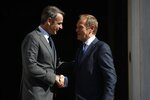 Greece's Prime Minister Kyriakos Mitsotakis, left, welcomes the European Council President Donald Tusk during their metering at Maximos Mansion in Athens, Wednesday, Oct. 9, 2019. EU leaders have demanded more
