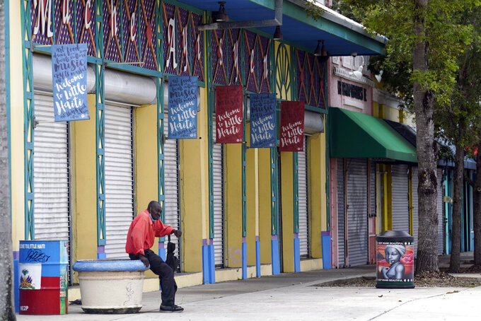 A man sits outside of the Little Haiti Cultural Center in the Little Haiti neighborhood of Miami, Wednesday, July 7, 2021, following the news that Haitian President Jovenel Moïse was assassinated in an attack on his private residence. (AP Photo/Lynne Sladky)