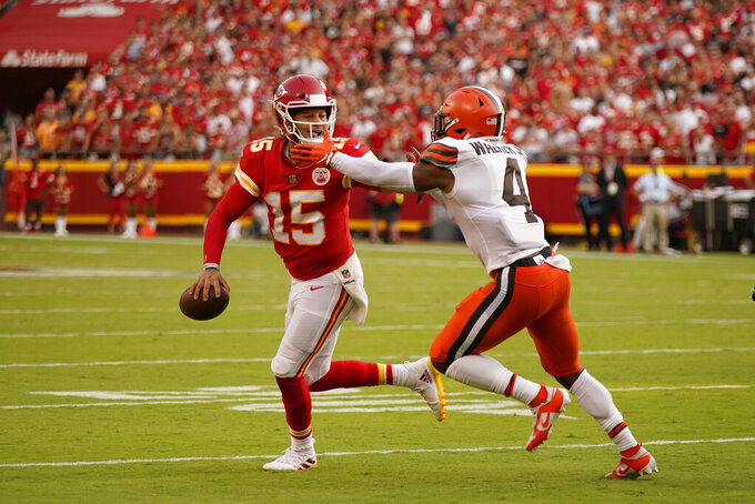 Kansas City Chiefs quarterback Patrick Mahomes (15) scrabbles away from Cleveland Browns linebacker Anthony Walker Jr. (4) during the second half of an NFL football game Sunday, Sept. 12, 2021, in Kansas City, Mo. (AP Photo/Charlie Riedel)