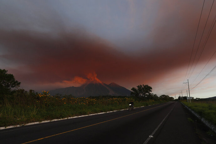 A cloud of red ash hovers over a highway close to the Volcan de Fuego, or Volcano of Fire, in El Rodeo, Guatemala, Monday, Nov. 19, 2018. About 4,000 residents fled the volcano Monday as red-hot rock and ash spewed into the sky and cascaded down the slopes toward an area devastated by a deadly eruption earlier this year. (AP Photo/Moises Castillo)
