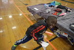 In this June 13, 2019 photo, a migrant boy plays inside the Portland Exposition Building in Portland, Maine. Maine's largest city has repurposed the basketball arena as an emergency shelter in anticipation of hundreds of asylum seekers who are headed to the state from the U.S. southern border. Most are arriving from Congo and Angola. (AP Photo/Elise Amendola)