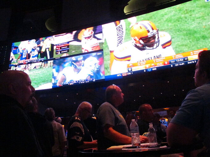 This Sept. 9, 2018 photo shows football fans watching the action on wall-mounted video screens in the sports betting lounge at the Ocean Resort Casino in Atlantic City, N.J. A report released Feb. 2, 2021 by the American Gaming Association predicts fewer Americans will bet on this year's Super Bowl, a decrease driven largely by fewer people back at work in offices where betting pools are circulated. But the report also predicts a record amount will be wagered online this year. (AP Photo/Wayne Parry)
