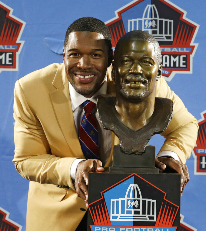 FILE - In this Aug. 2, 2014, file photo, Hall of Fame inductee Michael Strahan poses with his bust during the Pro Football Hall of Fame enshrinement ceremony in Canton, Ohio. The gap-toothed Strahan became a Hall of Famer, making four All-Pro teams, seven Pro Bowls, and winning NFL Defensive Player of the Year in 2001. He set a franchise record with 141 1/2 sacks, including the single-season best of 22 1/2 in 2001. (AP Photo/Tony Dejak, File)