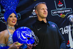 Boise State head coach Bryan Harsin poses alongside showgirl Jennifer Autry ahead of the Las Vegas Bowl NCAA college football game in Las Vegas, Tuesday, Dec. 17, 2019. (Chase Stevens/Las Vegas Review-Journal via AP)