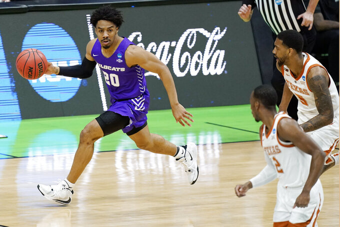 Abilene Christian's Coryon Mason (20) moves the ball up the court during the first half of a college basketball game against Texas in the first round of the NCAA tournament at Lucas Oil Stadium in Indianapolis Saturday, March 20, 2021. (AP Photo/Mark Humphrey)