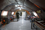 Iranian army soldiers work in a temporary 2,000-bed hospital for COVID-19 coronavirus patients set up by the army at the international exhibition center in northern Tehran, Iran, on Thursday, March 26, 2020. (AP Photo/Ebrahim Noroozi)