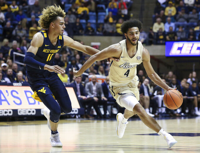 West Virginia's Emmitt Matthews Jr., left, defends against Akron's Tyler Cheese during the second half of an NCAA college basketball game, Friday, Nov. 8, 2019, in Morgantown, W.Va. (AP Photo/Kathleen Batten)