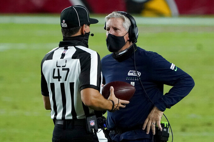 Seattle Seahawks head coach Pete Carroll talks with line judge Tim Podraza (47) during the second half of an NFL football game against the Arizona Cardinals, Sunday, Oct. 25, 2020, in Glendale, Ariz. (AP Photo/Rick Scuteri)
