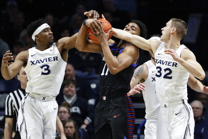 DePaul's Eli Cain (11) rebounds against Xavier's Quentin Goodin (3) and Ryan Welage (32) during the first half of an NCAA college basketball game, Saturday, Feb. 9, 2019, in Cincinnati. (AP Photo/John Minchillo)