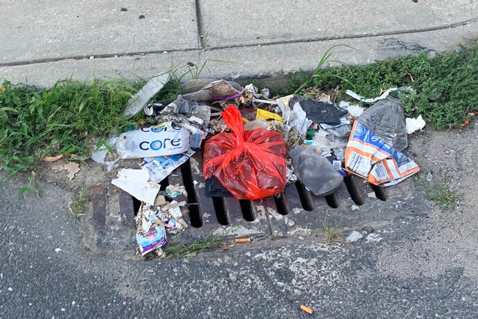 Trash rests on a street Tuesday, July 28, 2020, in Philadelphia. The COVID-19 pandemic has frustrated efforts to keep Philadelphia's streets clear of garbage this summer. People are staying home and generating more garbage, but the sanitation department has been shorthanded and workers have fallen behind picking up household trash and recyclables. Residents complain about the stink and the flies. (Kara Kneidl via AP)