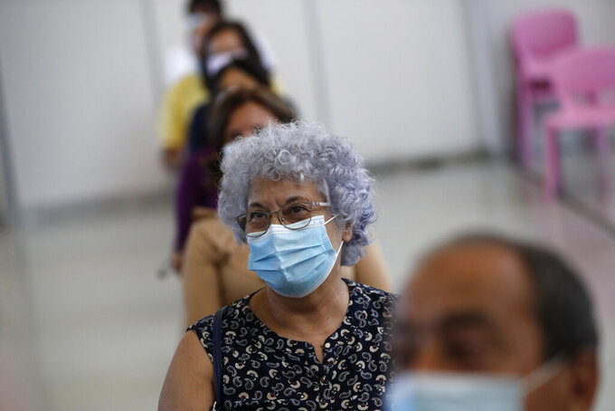People wait in a recovery area after getting shots of the Johnson & Johnson vaccine at an inoculation center operated by the Portuguese armed forces at Lisbon University's sports stadium, Wednesday, June 23, 2021. The Lisbon region's recent surge in COVID-19 cases is powering ahead, with new infections pushing Portugal's number of daily cases to a four-month high, as a report by health experts found fault with the government's pandemic response. (AP Photo/Armando Franca)