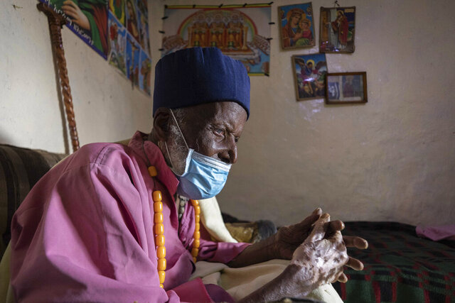 Centenarian Tilahun Woldemichael crys as he prays to God after spending weeks in hospital recovering from the coronavirus, at his house in Addis Ababa, Ethiopia Saturday, June 27, 2020. The Ethiopian monk believed to be 114 years old has survived the coronavirus and was discharged from a hospital on Thursday, having received oxygen and dexamethasone, a cheap and widely available steroid that researchers in England have said reduced deaths by up to one third in severely ill hospitalized patients. (AP Photo/Mulugeta Ayene)